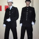"Photo:Two Brighton Police uniforms. On the right a ""dog collar"" uniform (pre 1953) - on the left - an open collar uniform (post 1953)"