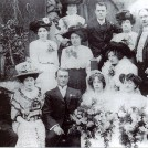Photo:Wedding of Rose Ray and Samuel Wood. In front row, next to Samuel, is Rose's cousin Lulu, and next to her is her husband George Kelsey. Top row, on right is Rose's brother Jim and his wife Minnie (from previous wedding photo).
